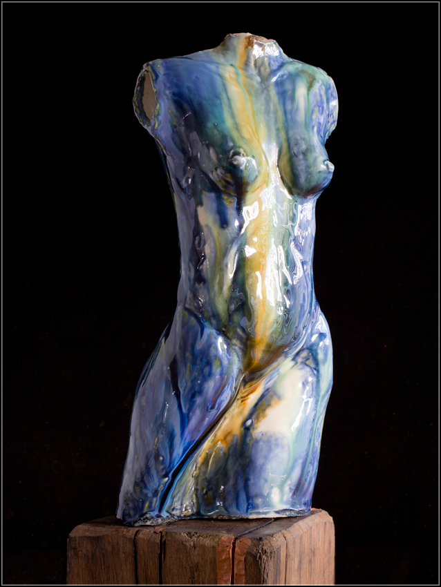 porcelain female figure, on found wood plinth, with metal decoration.