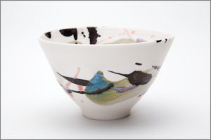 small porcelain bowl with red, black and blue glazes. Approximately 5-7 cm diameter.